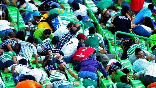 Zděšení fanoušci na tribuně při zápasu v Mexiku se schovávají před střelbou.