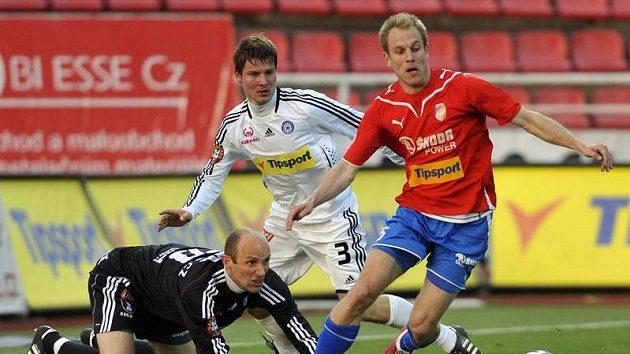 Plzeňský Daniel Kolář (v červeném) operuje s míčem před olomouckým gólmanem Tomášem Lovásikem a obráncem Pavlem Dreksou. Ilustrační foto.