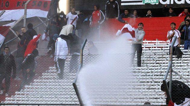 Fanoušky fotbalového týmu River Plate kropí hasiči vodou na stadiónu Monumental.