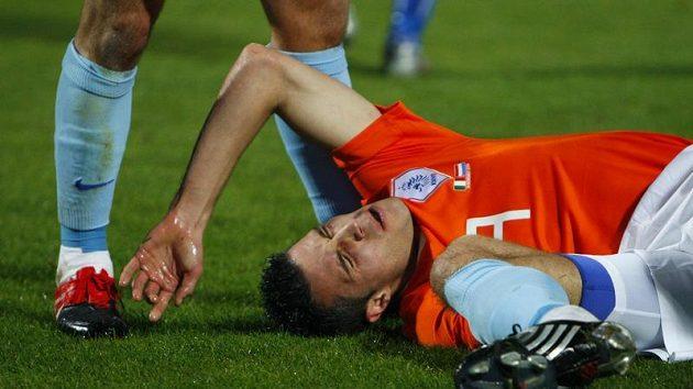 Robin van Persie leží v bolestech na trávníků během přátelského zápasu s Itálií