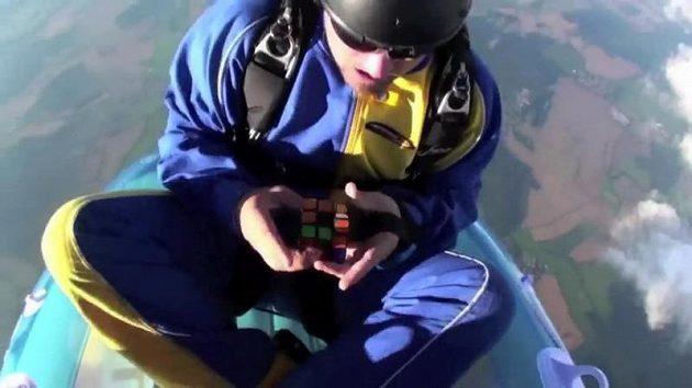Parašutista řeší Rubikovu kostku při volném pádu.