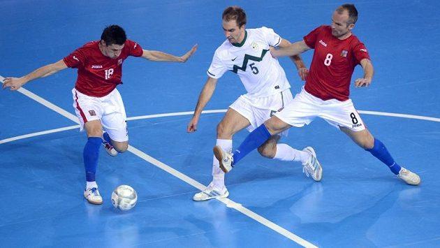 Michal Balej (vlevo) a Marek Kopecký (vpravo) z českého týmu bojují o míč se Slovincem Kristjanem Čujecem.