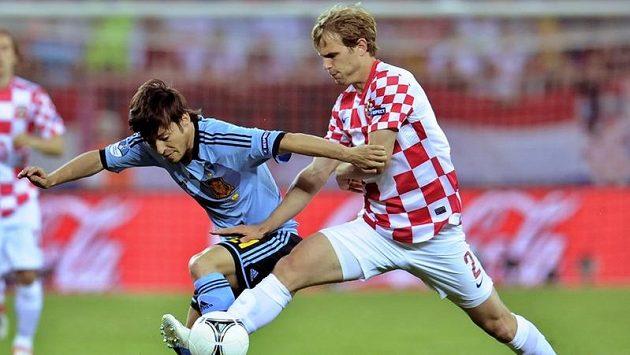 Španěl David Silva bojuje o míč s Ivanem Striničem.