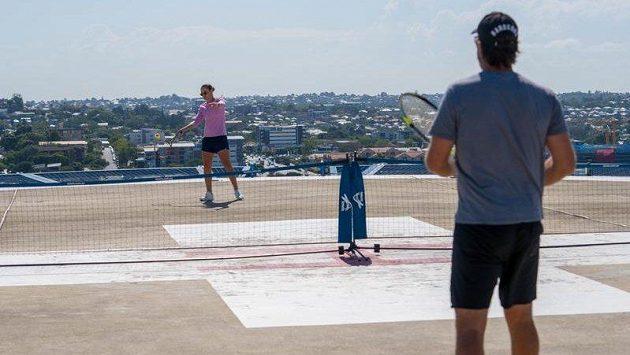 Světová jednička Ashleigh Bartyová (dále) na střeše nemocnice hraje s Patrickem Rafterem.