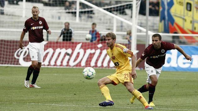 Jan Svatonský z Dukly (ve žlutém) si kryje míč před sparťanem Josefem Hušbauerem.