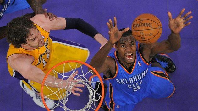 Basketbalista Oklahomy City Thunder Serge Ibaka (vpravo) v podkošovém souboji s Paulem Gasolem z LA Lakers.