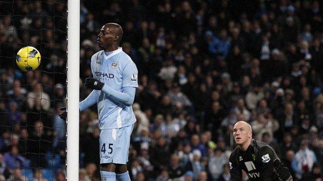 Útočním Manchesteru City Mario Balotelli (vlevo) střílí do sítě brankáře Norwiche Johna Ruddyho branku ramenem.