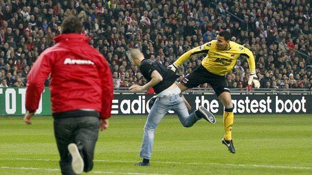 Brankář Alkmaaru Esteban Alvarado sráží fanouška, který vběhl na hřiště.