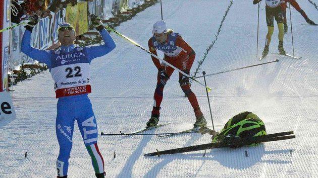 Italský sdruženář Alessandro Pittin (vlevo) oslavuje vítězství v závodu SP v Chaux-Neuve. Za cílovou čárou leží těsně druhý Francouz Jason Lamy-Chappuis.