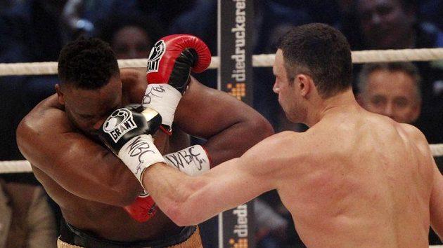 Dereck Chisora se kryje před Vitalijem Kličkem v souboji o světový titul v těžké váze.