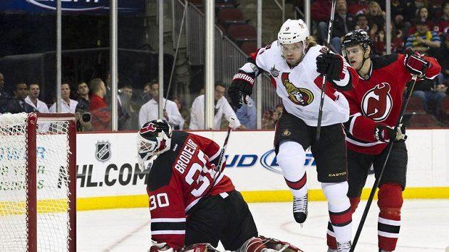 Útočník Ottawy Milan Michálek přeskakuje gólmana New Jersey Martina Brodeura poté, co vstřelil gól.