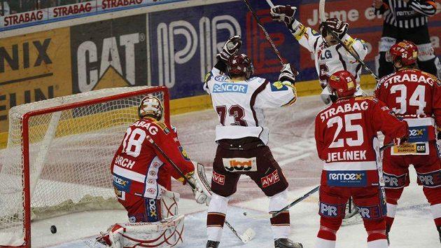 Hokejisté Sparty se radují, puk se zastavil v brance Slavie. Gólman Dominik Furch se jen bezmocně ohlíží.