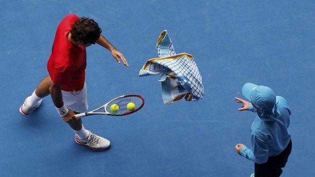 Roger Federer hází ručník sběrači míčků.