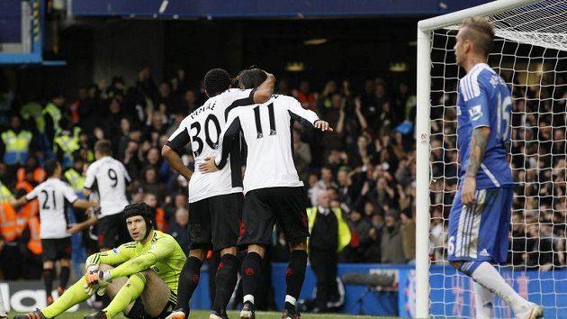 Zklamaný gólman Chelsea Petr Čech sedí na trávníku, zatímco hráči Fulhamu slaví vyrovnávací gól.