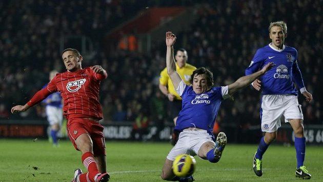 Gastón Ramírez (vlevo) ze Southamptonu střílí na bránu. Ránu se mu snaží zblokovat Leighton Baines z Evertonu (druhý zprava). Přihlíží Phil Neville (vpravo).
