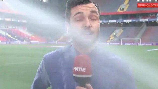 Reportér ruské televize Jevgenij Jevnevič dostal během živého vstupu sprchu od automatického zavlažovacího systému.