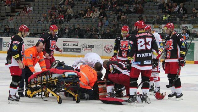 Přivolaní lékaři a záchranáři ošetřují zraněného hradecckého obránce Petera Mikuše.