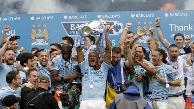 Kapitán Manchesteru City Vincent Kompany drží nad hlavou trofej pro vítěze Premier League.