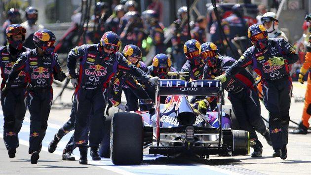 Mechanici Red Bullu tlačí vůz Marka Webbera zpět do boxu poté, co australskému jezdci upadlo špatně upevněné kolo.