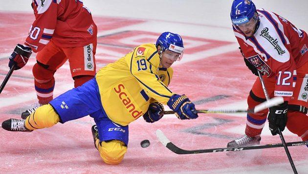 Švédský hokejový reprezentant Patrik Zackrisson (ve žlutém) se vrhl v souboji s českým týmem do cesty puku na Švédských hrách. Vše sleduje Radek Faksa (vpravo).