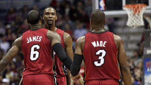Chris Bosh přijímá gratulace od spoluhráčů z Miami LeBrona Jamese a Dwyanea Wadea.