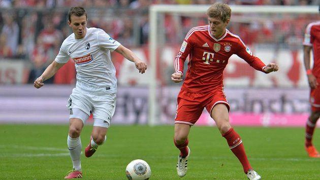 Český fotbalista Vladimír Darida (vlevo) v dresu Freiburgu bojuje o míč s Tonim Kroosem z mistrovského Bayernu.