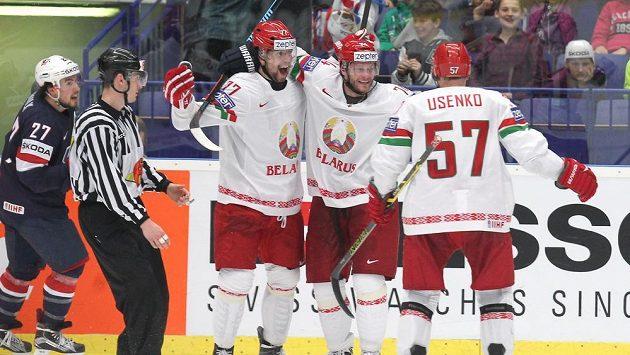 Hokejisté Běloruska (zleva) Alexandr Kitarov, Sergej Kosticyn a Ivan Usenko se radují z gólu proti Spojeným státům.