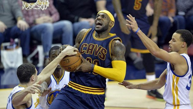Basketbalista Clevelandu LeBron James se prosazuje přes Klaye Thompsona (vlevo) a Stephena Curryho (30) z Golden State