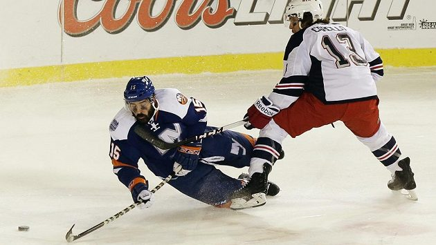 Útočník New Yorku Islanders Cal Clutterbuck (vlevo) padá na led, přesto ještě stihne přihrát na gól Brocku Nelsonovi.