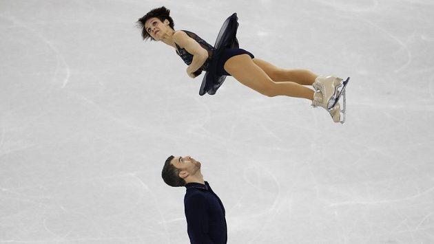 Kanadská krasobruslařka Meagan Duhamelová vysoko ve vzduchu nad svým partnerem Erikem Radfordem při olympijské soutěži družstev.