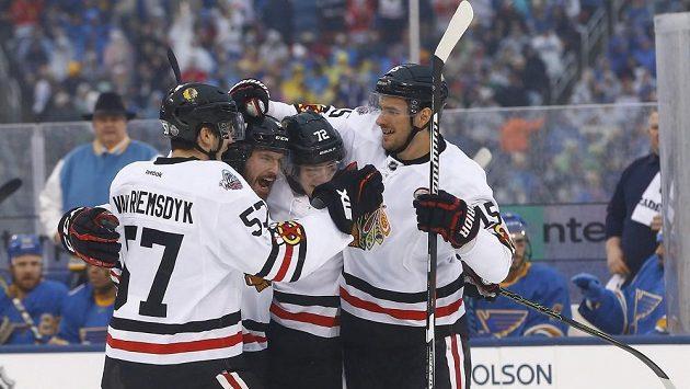 Obránce Chicaga Michal Kempný (druhý zleva) se raduje se spoluhráči z gólu proti St. Louis v zápase NHL, který se hrál pod širým nebem.