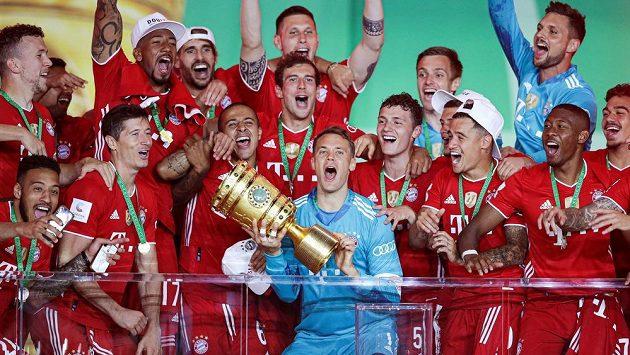 Brankář Manuel Neuer (uprostřed s trofejí) oslavuje se spoluhráči z Bayernu Mnichov triumf v Německém poháru. Ilustrační foto.
