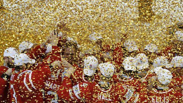 Hokejisté Kanady s pohárem mistrů světa skrytí v dešti zlatých konfet.