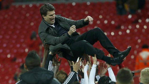 Trenér Michael Laudrup létá nad hlavami fotbalistů Swansea.