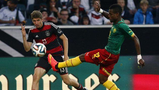 Němec Thomas Müller (vlevo) sleduje Henriho Bedima z Kamerunu, jak zpracovává míč v přípravném utkání před MS v Brazílii.