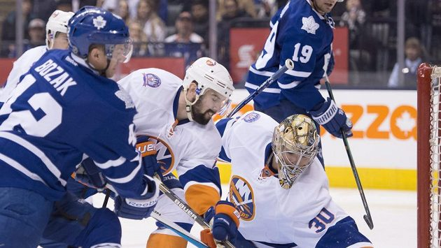 Útočník Toronta Tyler Bozak (vlevo) se snaží překonat brankáře New Yorku Islanders Michala Neuvirtha. Uprostřed je obránce Ostrovanů Nick Leddy.