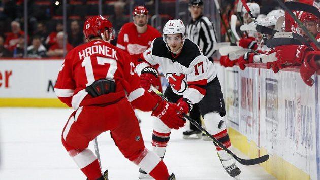 Kenny Agostino z New Jersey se snaží obejít českého obránce Detroti Filipa Hronka v zápase NHL.