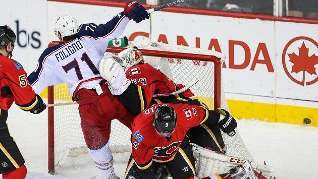 Brankář Calgary Reto Berra (vzadu vpravo) se snaží zabránit ve skórování Nicku Folignovi z Columbusu. Vpravo dole obránce Flames Ladislav Šmíd.