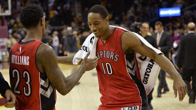 Hráči Toronta Raptors DeMar DeRozan (číslo 10) a Louis Williams (23) oslavují cennou výhru na palubovce Clevelandu.