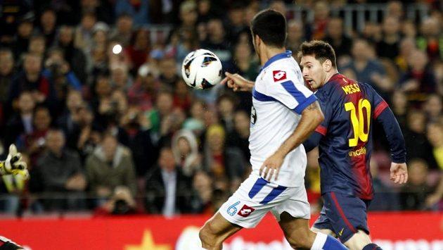 Lionel Messi (vpravo) skóruje přes obránce Aythamiho do sítě La Coruny.