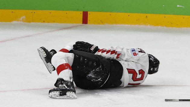 Rakouský hokejista Steven Strong leží na ledě po faulu Svena Andrighettiho v zápase se Švýcarskem.