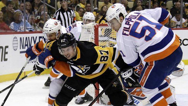 Hvězda Pittsburghu i celé NHL Sidney Crosby bojuje s přesilou hráčů New York Islanders.