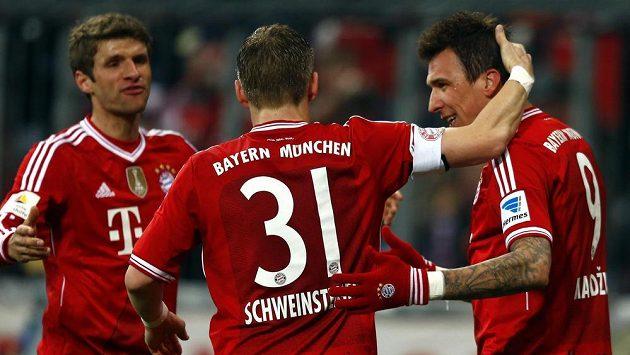 Thomas Müller (vlevo) a Bastian Schweinsteiger gratulují svému spoluhráči z Bayernu Mnichov Mariu Mandžukičovi k brance, kterou vstřelil proti Leverkusenu.