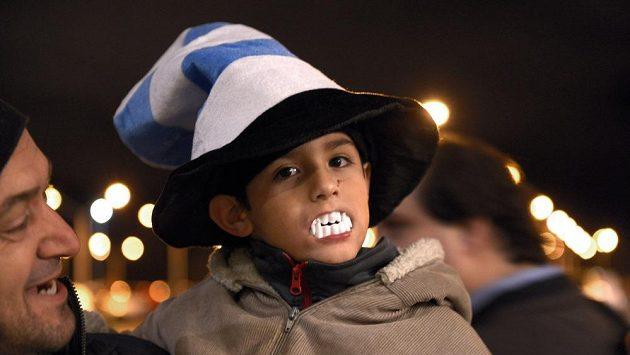 Malý chlapec vyjadřuje na letišti v Montevideu podporu Luisi Suárezovi. Nasadil si plastové upíří zuby.