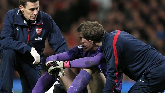 Brankář Arsenalu Wojciech Szczesny (uprostřed) je po srážce s obráncem Manchesteru United Philem Jonesem v péči lékařů.