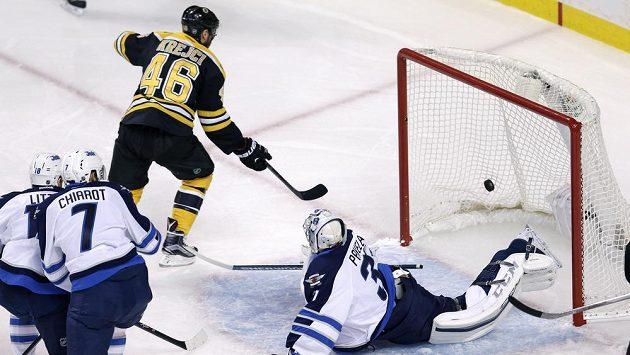 Centr Bostonu Bruins center David Krejčí překonává brankáře Jets Ondřeje Pavelce.