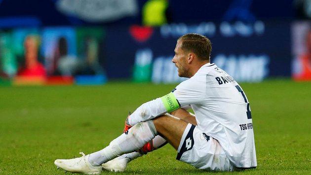 Hoffenheim prohrál bundesligový zápas s Frankfurtem, zklamaný Oliver Baumann sedí po závěrečném hvizdu na trávníku.