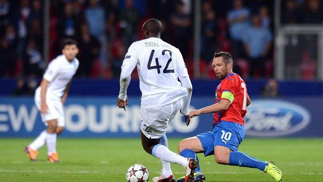 Plzeňský záložník Pavel Horváth (vpravo) se skluzem snaží vypíchnout míč středopolaři Manchesteru City Yaya Tourému během zápasu Ligy mistrů.