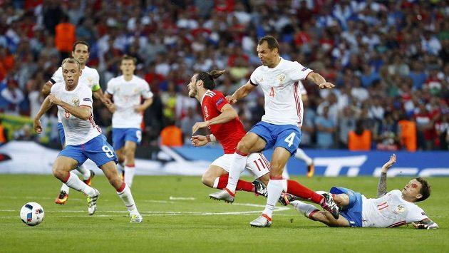 Rus Sergej Ignaševič zastavuje unikajícího Garetha Balea z Walesu.