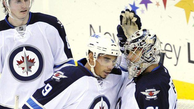 Gólman Winnipegu Ondřej Pavelec (vpravo) přijímá od spoluhráčů gratulace po vyhraném duelu s New Jersey.